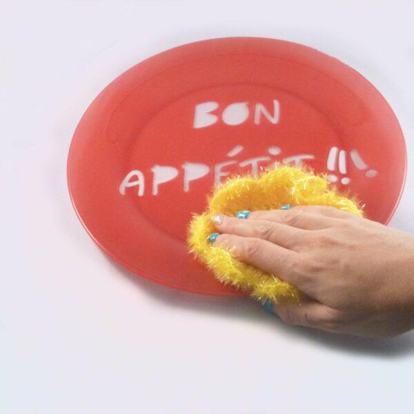 éponge-vaisselle-forme-ronde-couleur-jaune-avec-la-main-sur-assiette